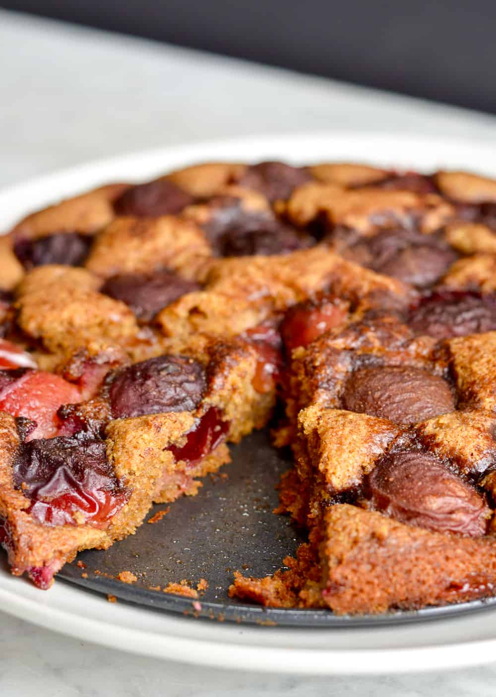 plum torte with piece cut